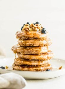 Stack of fluffy vegan pancakes topped with blueberries, walnuts and maple syrup on a plate.