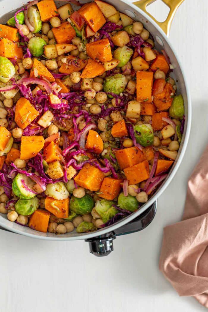 Chickpeas and a grainy dijon maple sauce in a skillet with sweet potato, brussels sprouts, red onion and cabbage.