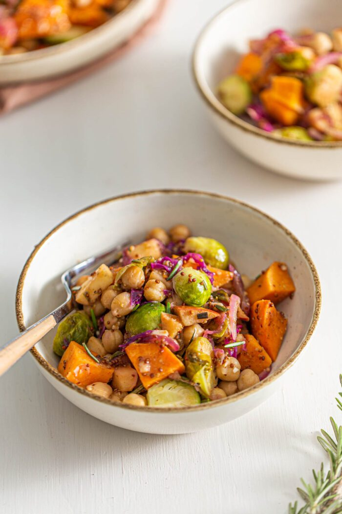Small dish of chickpeas, sweet potato, Brussels sprouts, cabbage and red onion in maple dijon sauce.