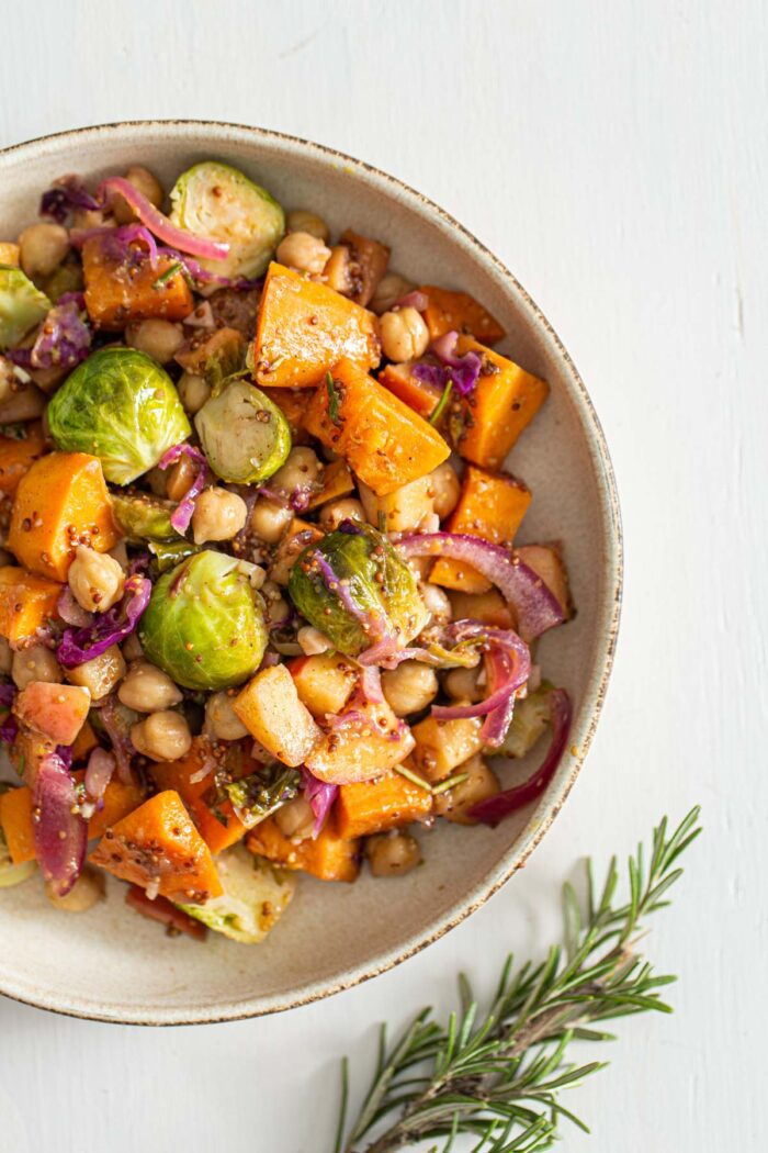 Overhead view of a dish of chickpeas, sweet potato, Brussels sprouts, cabbage and red onion in maple dijon sauce.