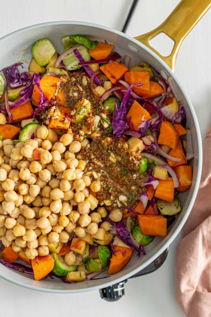 Chickpeas and a grainy maple dijon sauce in a skillet with sweet potato, brussels sprouts, red onion and cabbage.