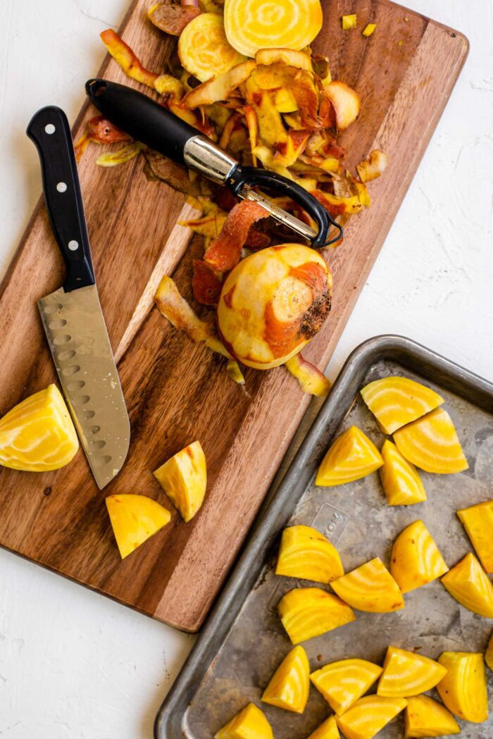 Large peeled golden beets on a cutting board with a knife and peeler.