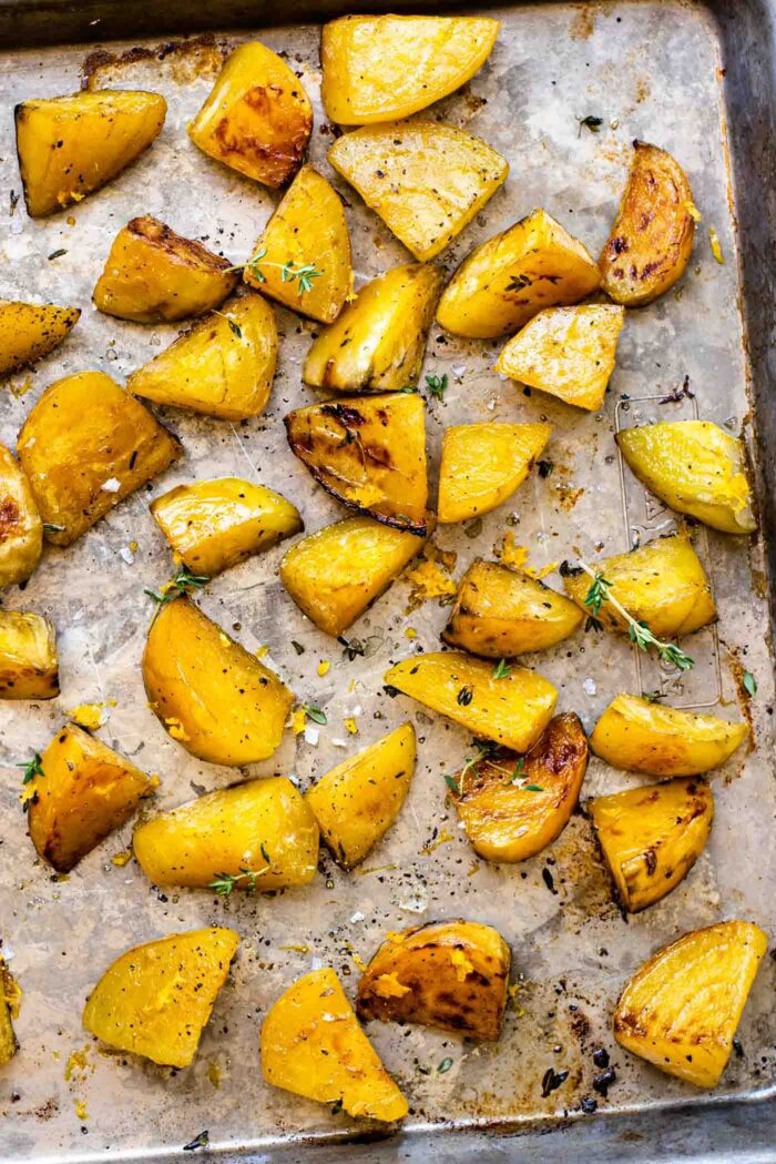 Roasted golden beets with sprigs of fresh thyme on a baking pan.