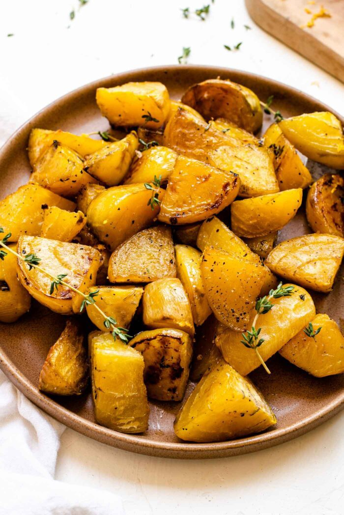 Plate of roasted golden beets with fresh thyme.