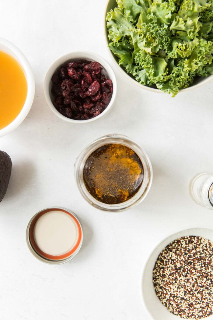 Overhead view of balsamic maple dressing in a small jar, bowl of kale and bowl of cooked quinoa.