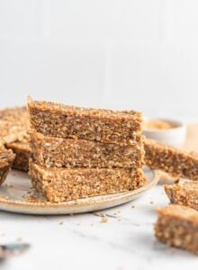 Stack of 3 homemade energy bars on a plate with more bars scattered around them.