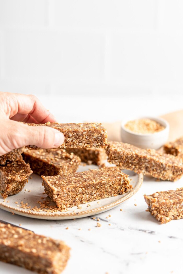 Hand picking an energy bar from a plate of bars.