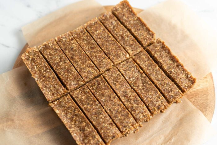 Sliced energy bars on a parchment paper-lined round cutting board.