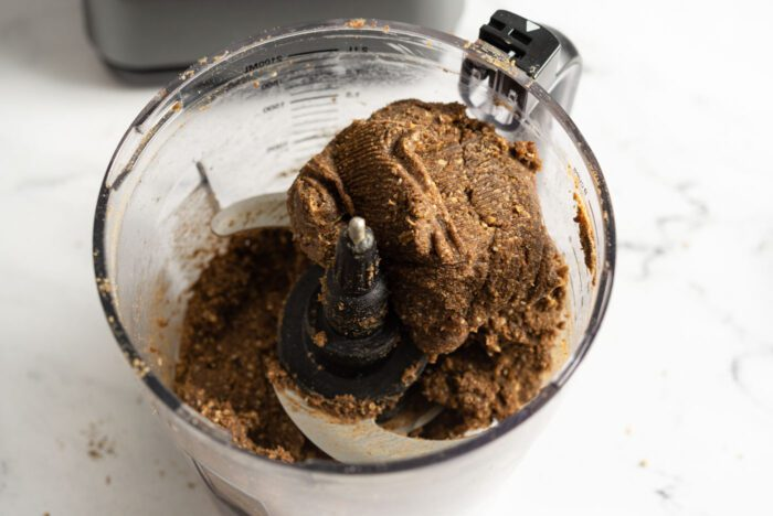 Thick dough made from dates, almonds and hemp protein powder in a food processor.
