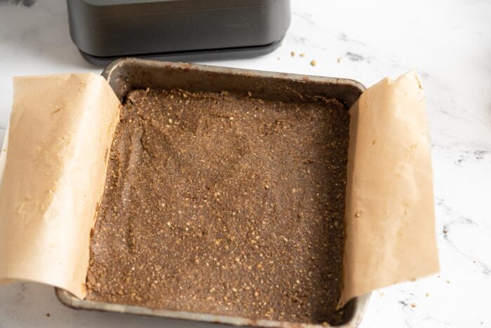 No-bake energy bars in a square baking pan lined with parchment paper.