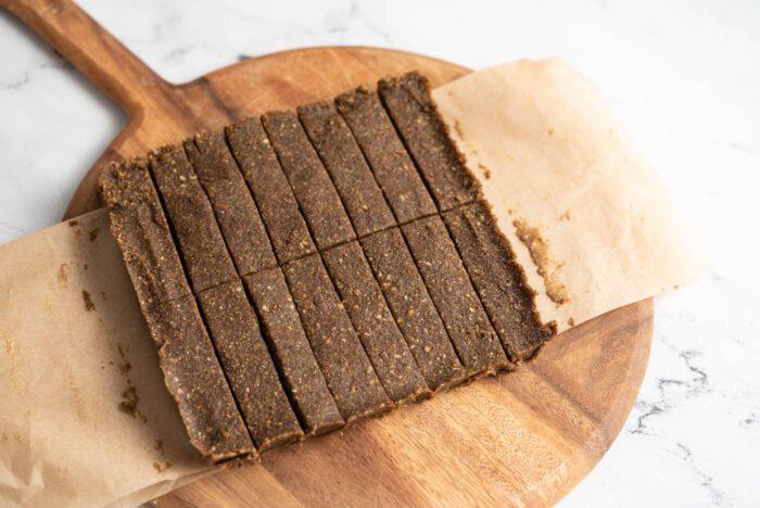 A slab of no-bake hemp protein bars cut into 16 portions on a cutting board.