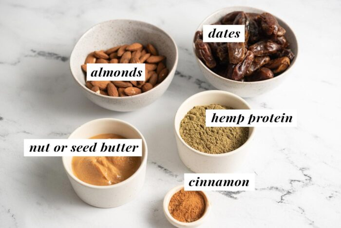 Almonds, hemp protein, dates, cinnamon and peanut butter each in a small dish. Each ingredient is labelled with text.