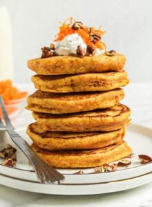 Stack of 6 thick carrot pancakes on a small plate. Fork rests on the plate.