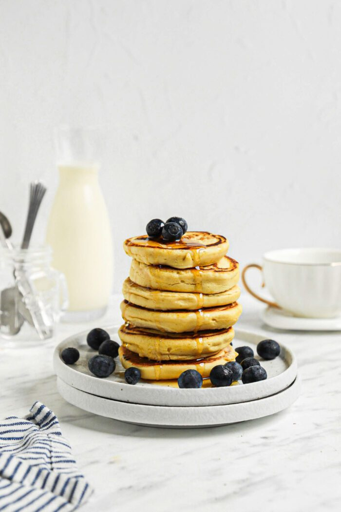Stack of 6 thick chickpea flour pancakes topped with blueberries and maple syrup on a small plate.