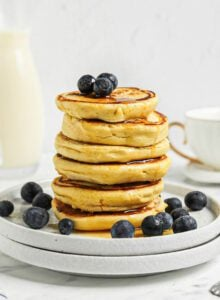 Stack of 6 thick chickpea flour pancakes topped with blueberries and maple syrup on a small plate. A jug of milk and a coffee cup are in the background.