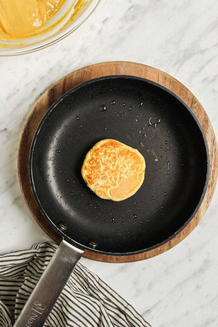 One garbanzo bean flour pancake cooking in a hot skillet.