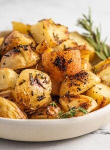 Bowl of crispy roasted lemon rosemary potatoes with a sprig of rosemary resting in the bowl.
