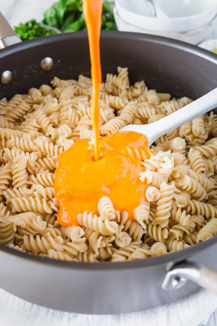Pouring red pepper pasta sauce over a large skillet of cooked fusilli.