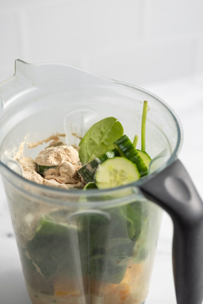 Cucumber, spinach, mango chunks and protein powder in a blender container.