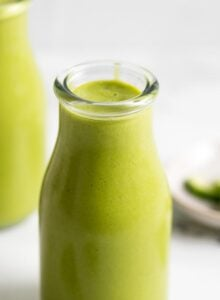 Two jars of creamy green mango pineapple smoothie with a few pieces of spinach scattered around them.