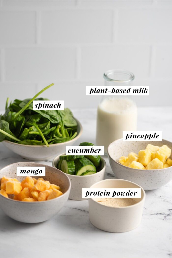 Visual list of ingredients for making a vegan mango pineapple smoothie recipe with almond milk, spinach and cucumber.